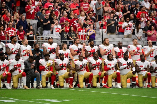 Members of the San Francisco 49ers kneel during the National Anthem prior to a game against the Arizona Cardinals at University of Phoenix Stadium. (Photo via Reuters)