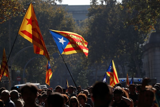 Catalan separatist flags are waved as demonstrators gather outside the Catalan regional parliament in Barcelona, Spain. (Image: Reuters)