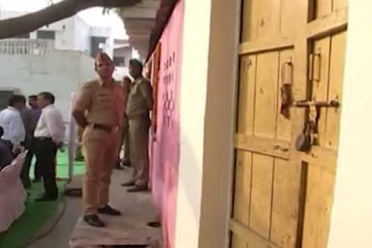 A policeman stands guard outside a locked house in Kachhpura village on Thursday morning. (Photo: CNN-News18)