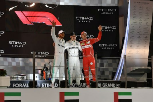 Mercedes' British driver Lewis Hamilton, Mercedes' Finnish driver Valtteri Bottas and Ferrari's German driver Sebastian Vettel celebrate on the podium at the end of the Abu Dhabi Formula One Grand Prix at the Yas Marina circuit on November 26, 2017. (Image: AFP)