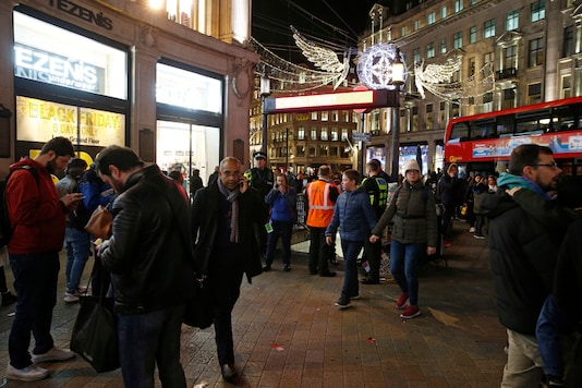 Police officers and members of the public walk near the entrance of Oxford Circus subway station in the west of London after it was reopened on Friday. (AP)