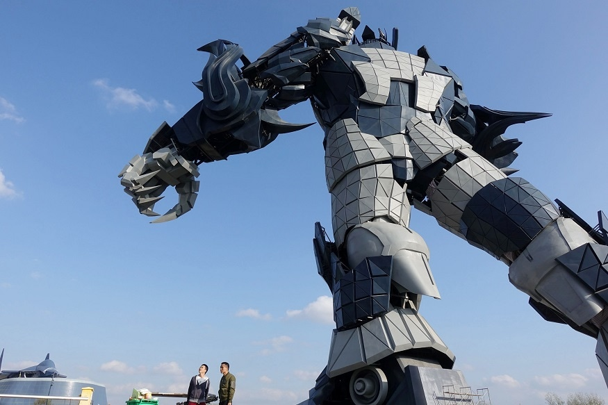 Staff members stand underneath a giant robot statue at the Oriental Science Fiction Valley theme park in Guiyang