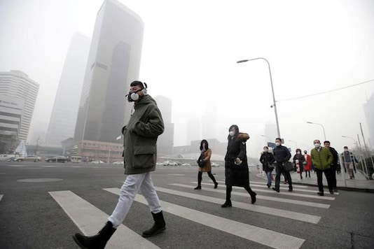 A man wearing a respiratory protection mask walks toward an office building during the smog after a red alert was issued in 2016. (Reuters)