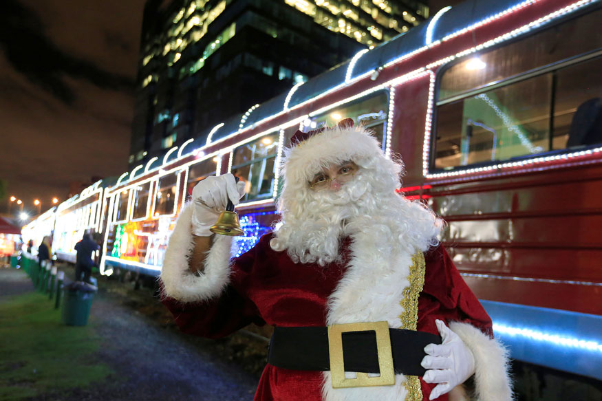 A man dressed as Santa Claus poses for photos near tourist train 'La Sabana' which is decorated with Christmas lights in Bogota, Colombia. (Image: Reuters)
