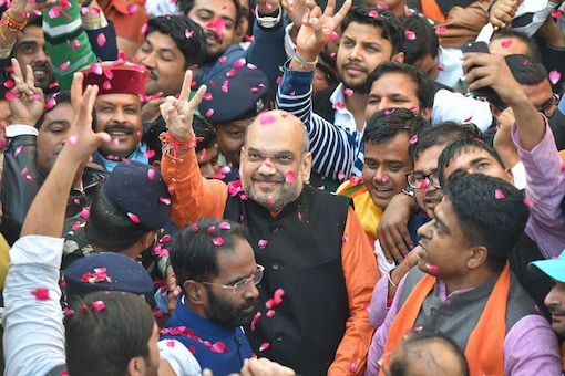 BJP President Amit Shah flashes victory sign as he is accorded warm welcome on his arrival at the party headquarters in New Delhi on Monday, after the party's victory in the Assembly elections in Gujarat and Himachal Pradesh (PTI Photo)
