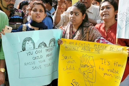 Parents of students hold placards during their mass gathering outside the premises of a high-profile school in Kolkata  (PTI Photo)