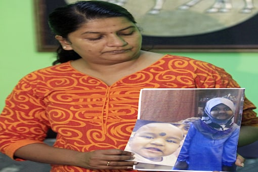 In this October 16, 2014, file photo, Indira Gandhi shows photos of her youngest daughter Prasana Diksa at her house in Ipoh, Perak state, Malaysia. Malaysia's top court in a landmark decision says both parents must consent to the religious conversion of a minor, ruling in favor of Hindu woman Gandhi whose ex-husband converted their three children to Islam. (AP Photo/Lai Seng Sin, File)
