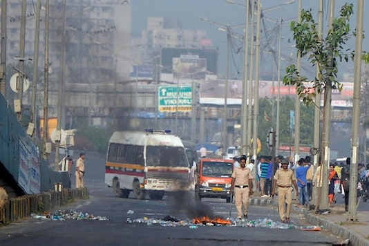 Policemen try to control the situation during the violent Dalit protests in Mumbai. (Image: PTI)