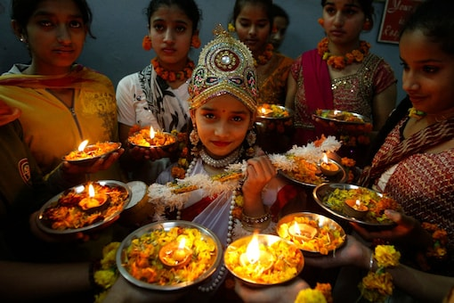 """School girls perform prayers on the eve of """"Saraswati Puja"""" festival at a school in Amritsar. (Image: Reuters)"""