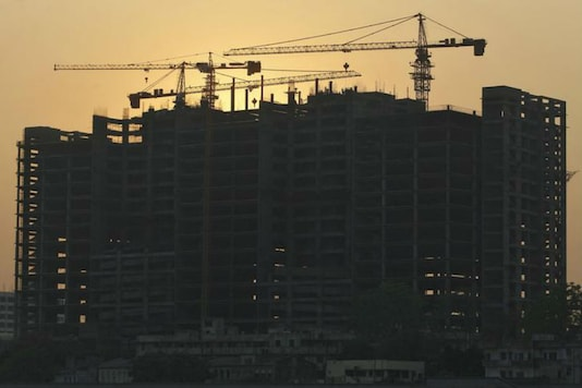 Cranes are silhouetted against the setting sun at the construction site of a hospital building in Ahmedabad. (File photo/Reuters)