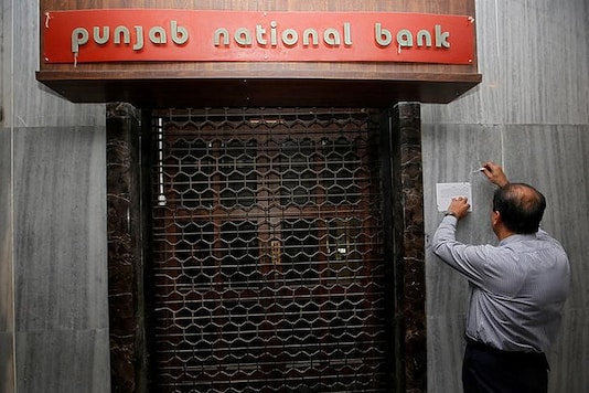 A man tries to remove a notice pasted on the wall of a Punjab National Bank branch after it was sealed by in Mumbai, India. (Reuters)