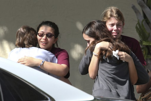 File Photo of students grieving outside Pines Trail Center where counselors interacted with them after Wednesday's mass shooting at Marjory Stoneman Douglas High School in Florida. (AP Photo)