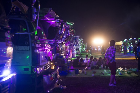 Families gathered in front of rows of custom-painted trucks at a fancy truck party in the Thai coastal province of Rayong. (Image: AFP Relaxnews)