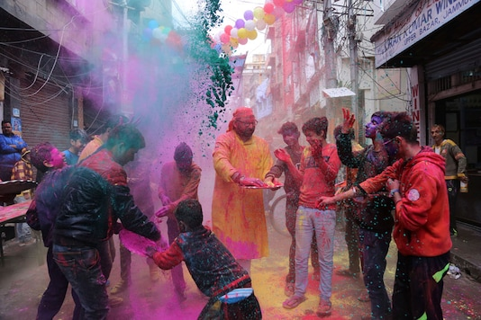 People play with colored powder during Holi festival celebrations. (Image: AP)