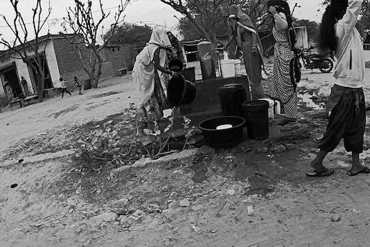 Women fetch water from a government-installed hand pump in Bhateri. In this part of Rajasthan, women are required to keep their head and face covered all the time.