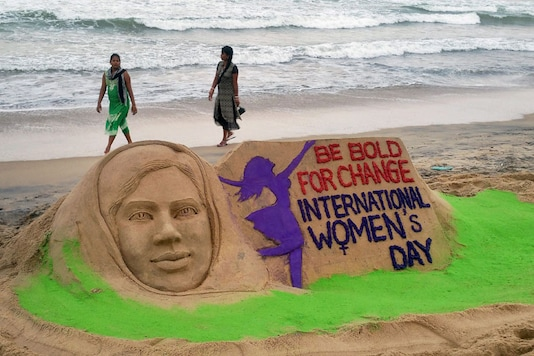 Sand artist Manas Sahoo makes a sand art on the eve of International Women's Day in Puri beach. (PTI Photo)