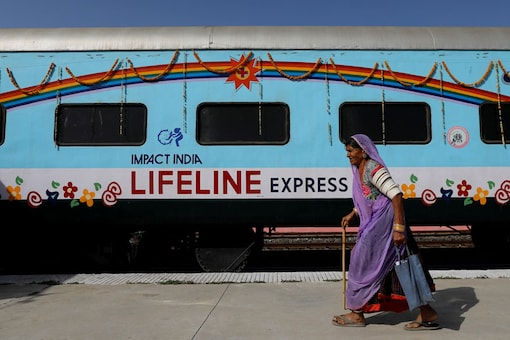 A patient walks past the Lifeline Express, a hospital built inside a seven-coach train, parked at a railway station in Jalore. (Reuters)