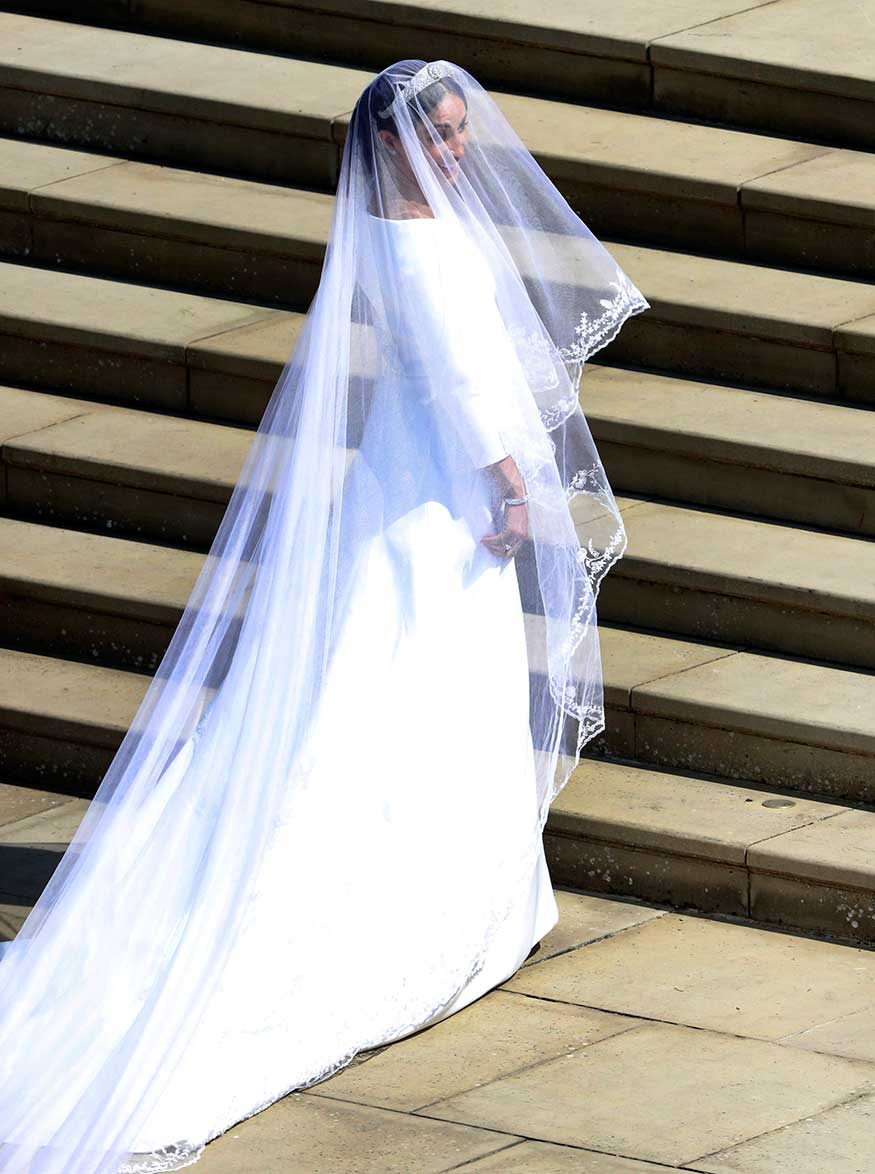 Hollywood star Meghan Markle walked down the nave of St. George's Chapel for her wedding to Prince Harry in a sleek silk boat-necked gown and long billowing veil designer by British designer Clare Waight Keller of Givenchy. (Image: AP)