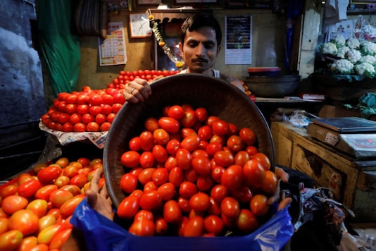 A vendor loads tomatoes in a bag for a customer at a wholesale vegetable market.  (File photo: Reuters)