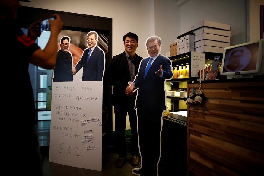 Cafe owner Kim Jeong-il takes photographs of a customer next to cardboard cutouts of North Korean leader Kim Jong Un and South Korean President Moon Jae-in at his coffee shop in Jeonju, South Korea, June 1, 2018. REUTERS/Kim Hong-Ji