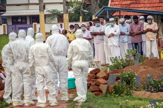 Relatives and hospital officals wear safety masks as they perform the last rites of a Nipah virus victim in Kozhikode. (PTI photo)