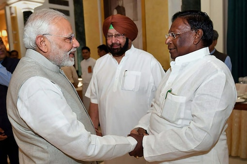 PM Narendra Modi exchanges greetings with Puducherry Chief Minister V Narayanasamy during the NITI Aayog meet in New Delhi on Sunday. (PTI Photo)