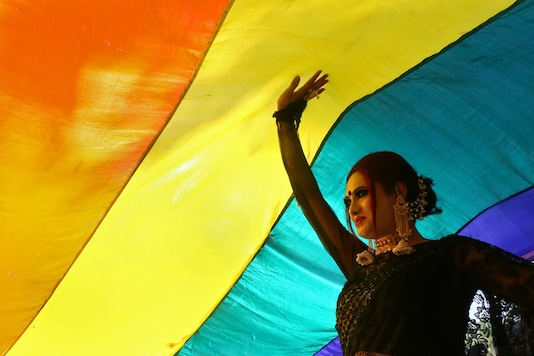 A participant walks under a rainbow flag during a pride parade in 2018. (Image: Reuters