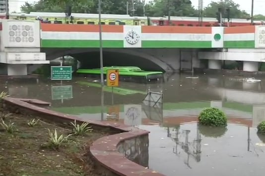 There were reports of several other vehicles including a bus getting stuck in a waterlogged road under Minto Bridge on Sunday morning. (Image: ANI)