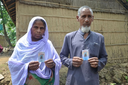 A couple displays their voter ID cards, which have been wrongly printed in a village in Barpeta ahead of the publication of final draft of NRC. (News18)