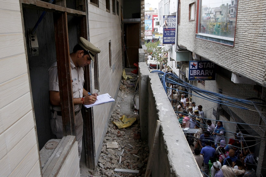A policeman writes notes in the house where the bodies of eleven members of a family were found dead in Burari (Reuters)