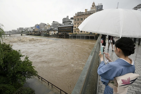 A kimono-clad woman using a smartphone takes photos of swollen Kamo River, caused by a heavy rain, from Shijo Bridge in Kyoto, western Japan. (Image: Reuters)