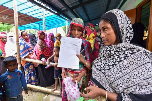People wait to check their names on the final draft of the state's National Register of Citizens after it was released, at an NRC Seva Kendra in Nagaon on July 30, 2018. (PTI Photo)