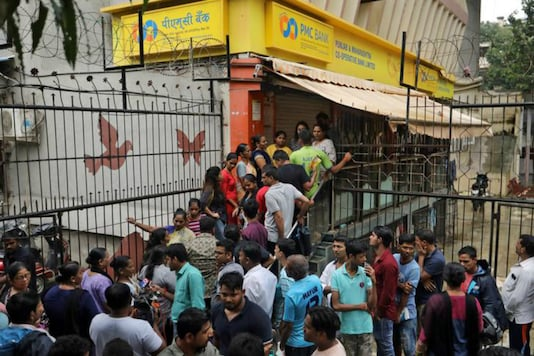 People wait outside a PMC Bank branch in Mumbai. (Reuters)