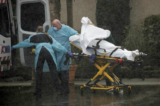 Medics transport a patient through heavy rain into an ambulance at Life Care Center of Kirkland, the long-term care facility linked to several confirmed coronavirus cases in the state, in Washington. (Reuters)