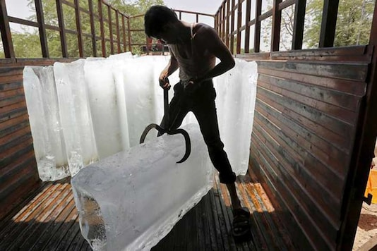 A worker of an ice factory loads an ice bar onto a truck to supply to a market on a hot summer day. (Image: Reuters)