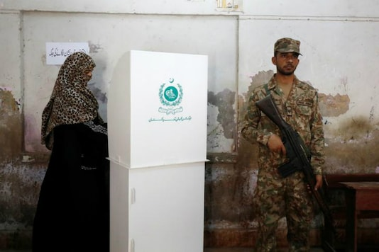 A woman votes next to a soldier at a polling station during the general election in Karachi, Pakistan, July 25, 2018. REUTERS/Akhtar Soomro