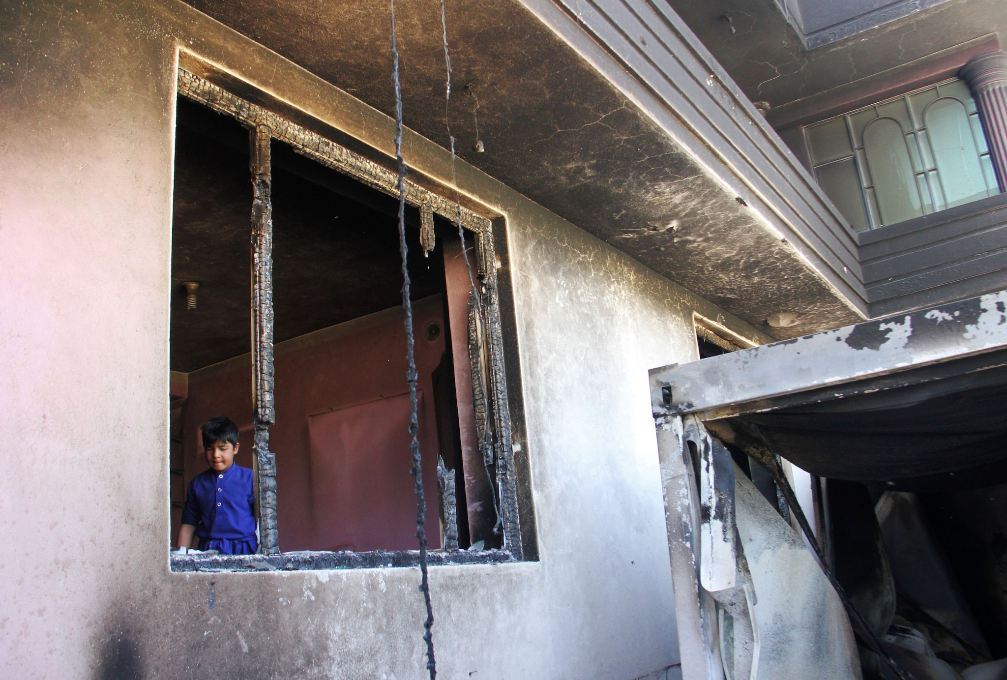 An Afghan boy is seen inside a burnt building after a Taliban attack in Ghazni city, Afghanistan
