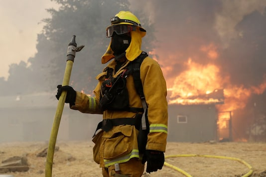 A firefighter with Pacifica Fire Department stands in front of a burning barn to prevent it from reaching a residence in Finley, California. (Image: AP)