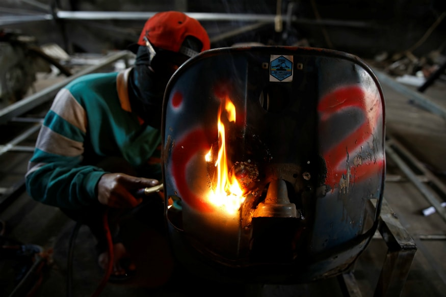 A mechanic works on turning an old Vespa bike into an extreme tank to sell at a workshop. (Image: Reuters)