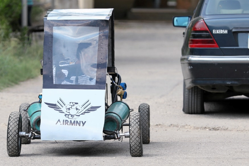 Mahmoud Yasser, mechanical engineering student from Helwan University, drives the air-powered vehicle which he helped design to promote clean energy and battle increasing gas prices, in Cairo, Egypt. (Image: Reuters)