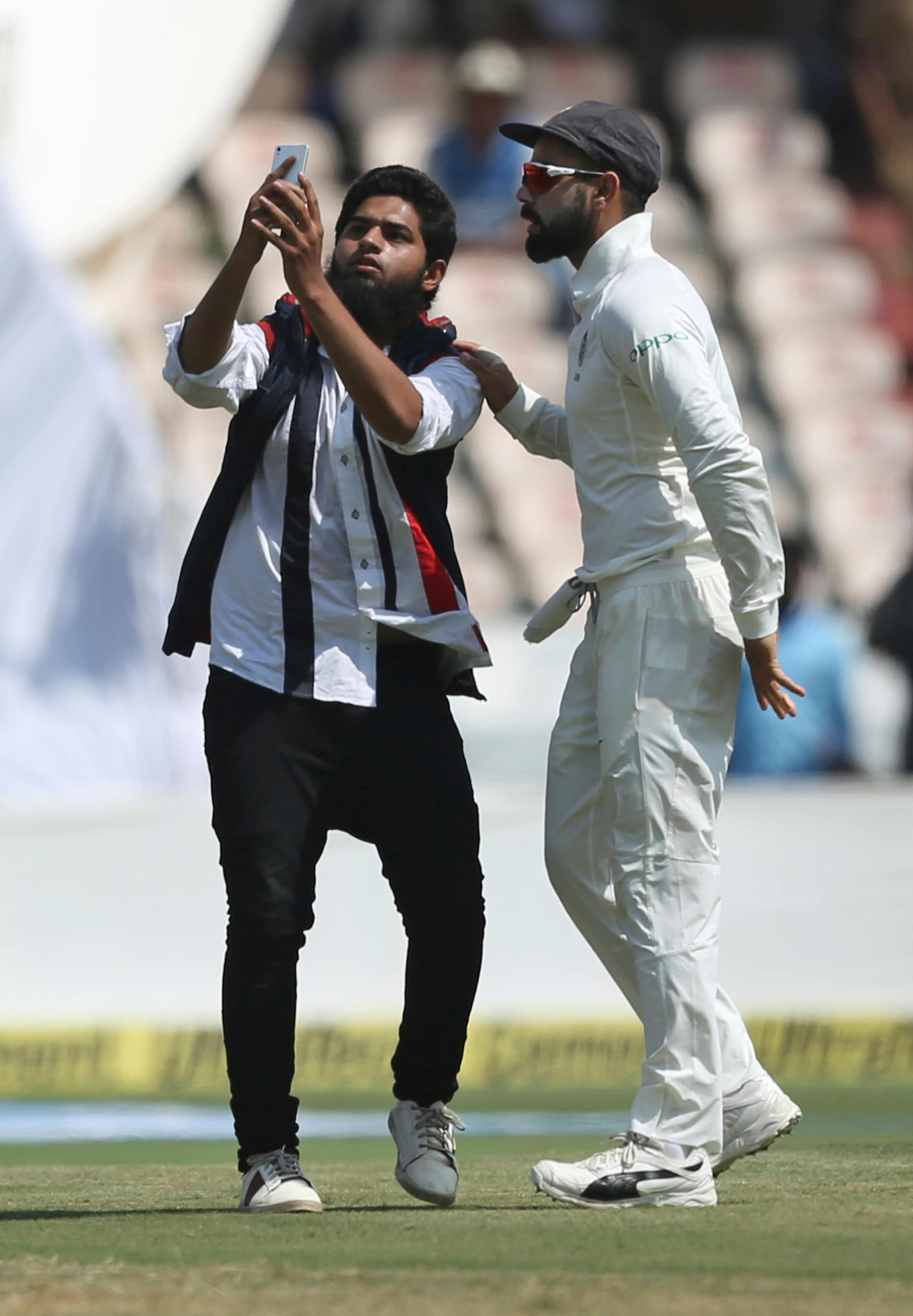 An Indian fan takes a selfie with cricketer Virat Kohli after running into the field disrupting the first day of the second cricket test match between India and West Indies in Hyderabad, India, Friday, Oct. 12, 2018. (AP Photo/Mahesh Kumar A.)