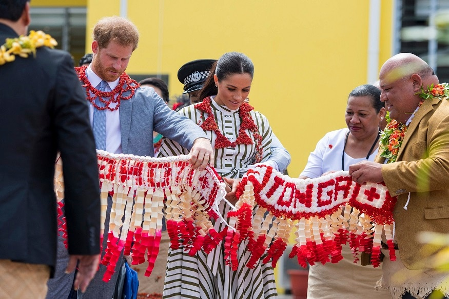 Britain's Prince Harry and Meghan, Duchess of Sussex are handed a ta'ovala, a traditional Tongan dress to be wrapped around their waist, at the Fa'onelua Convention Centre in Nuku'alofa, Tonga, Friday, Oct. 26, 2018. Prince Harry and his wife Meghan are on day 11 of their 16-day tour of Australia and the South Pacific. (Dominic Lipinski/Pool Photo via AP)