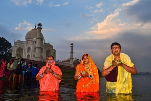 Agra: People offer prayers to the rising sun during the Chhath puja on the bank of River Yamuna in the backdrop of Taj Mahal, Agra. (Image: PTI)