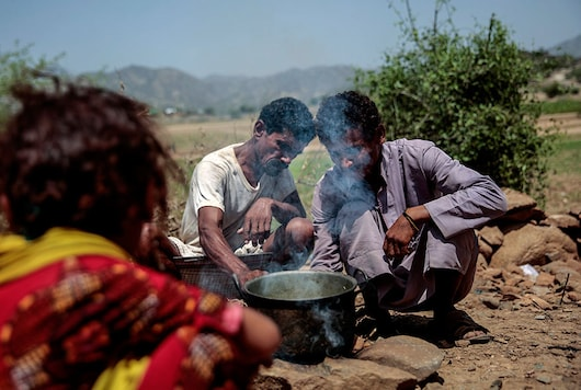 For representation: A man cooks Halas for his children, a climbing vine of green leaves, in Aslam, Hajjah, Yemen. Years of conflict has pushed the 29 million Yemenis to the brink of famine. (Image: AP file photo)