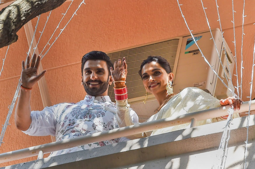 Newly-married Bollywood actors Ranveer Singh and Deepika Padukone greet their fans from the balcony of their residence, in Bengaluru November 20, 2018. (Image: PTI)