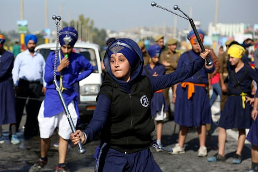 A Sikh girl displays traditional martial art skills during a religious procession ahead of the birth anniversary of Guru Nanak in Jammu. (Image: AP)