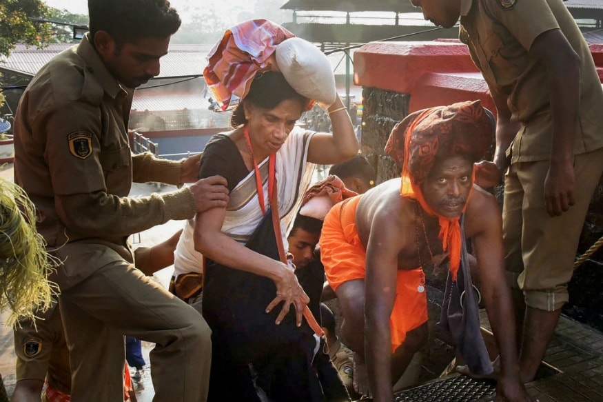 Police personnel assist devotees to climb up the 18 sacred steps of the Lord Ayyappa temple for offering prayers, on the 2nd day of Malayalam month of 'Vrischikom,' in Sabarimala, on Sunday. (PTI)