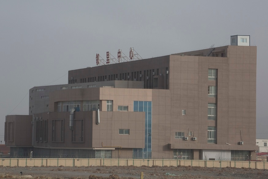 "A building with the words ""Neighborhood Center"" at the top is seen behind barbed wire fences in the Vocational Skills Education Training Service Center in western China's Xinjiang region."