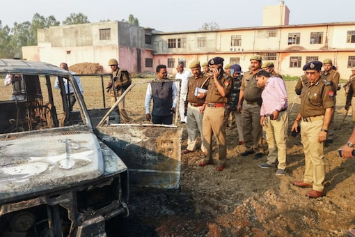 Policemen inspect the site after several vehicles were set on fire by a mob during a protest over alleged illegal cow slaughter in Bulandshahr on December 3.  (PTI)