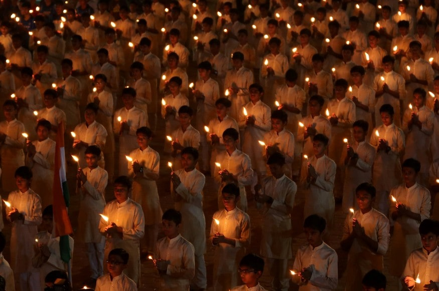 Students hold candles during a vigil to pay tribute to Central Reserve Police Force (CRPF) personnel who were killed in Pulwama terror attack in south Kashmir, inside a temple in Ahmedabad. (Image: Reuters)